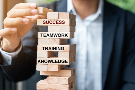 Businessman hand placing or pulling wooden block on the tower with text; Success, Teamwork, Training and Knowledge. Business concepts Imagens