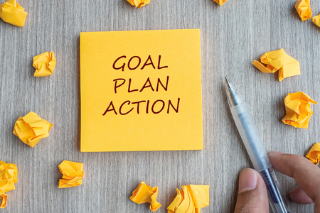 Goal, Plan, Action word on yellow note with Businessman holding pen and crumbled paper on wooden table background. Business Vision, Mission, Value, Strategy and Goal concept