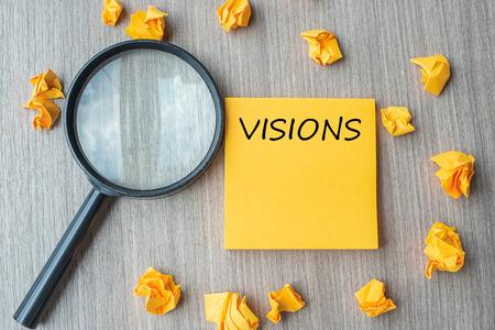 Visionswörter auf gelber Note mit zerbröckeltem Papier und Lupe auf Holztischhintergrund. SEO, Idee, Ziel, Strategie, Analyse, Keyword- und Content-Konzept Standard-Bild