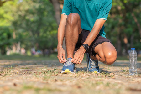 Young athlete man tying running shoes in the park outdoor, male runner ready for jogging on the road outside, asian Fitness walking and exercise on footpath in morning. wellness and sport concepts