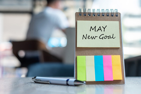 May New Goal  with note paper reminder template with pen on wooden table. Copy space for your text