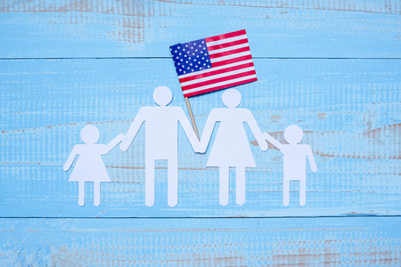 People or Family paper shape with flag of the United States of America on blue wooden background. USA holiday of Veterans, Memorial, Independence and Labor Day