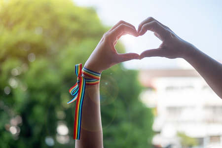 woman hands showing heart shape sign with LGBTQ Rainbow ribbon in the morning for Lesbian, Gay, Bisexual, Transgender and Queer community