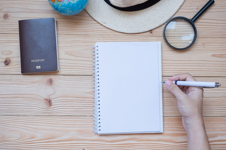 hand traveler writing  on notebook with accessories, Camera, Passport, Magnifying, smart Phone and hat on wooden table, Top view and copy space. Travel planning concept