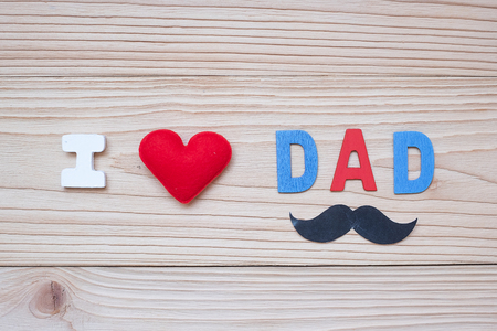 I Love DAD text with red heart shape and mustache on wooden background. Happy Fathers Day and International Mens Day concepts
