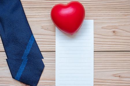 scheda vuota con cravatta blu e forma di cuore rosso su sfondo di legno con copia spazio per il testo. Concetti per la festa del papà e la Giornata internazionale dell'uomo Archivio Fotografico