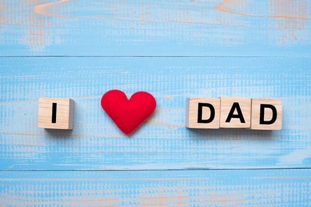 I Love DAD text with red heart shape on wooden background. Happy Father's Day and International Men's Day concepts