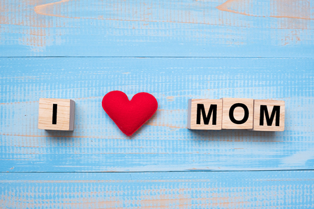 I Love MOM text with red heart shape on blue wooden background. Happy Mothers Day and International Womens Day concepts
