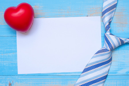 empty note paper with blue neckties and red heart shape on wooden background. Happy Father's Day and International Men's Day concepts
