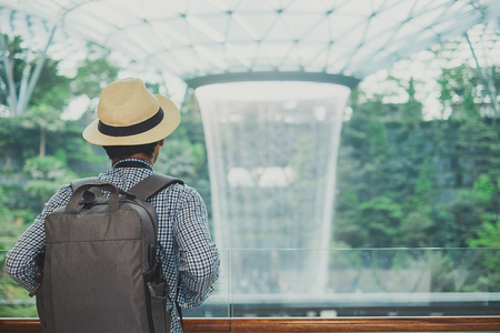 young man with bag and hat, Asian traveler standing and looking to beautiful rain vortex at Jewel Changi Airport, landmark and popular for tourist attractions in Singapore. Travel concept