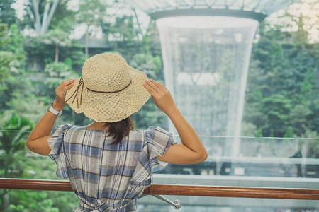 young woman wear blue dress and hat, Asian traveler standing and looking to beautiful rain vortex at Jewel Changi Airport, landmark and popular for tourist attractions in Singapore. Travel concept