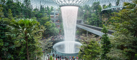 The Giant water fall HSBC Rain Vortex and beautiful green nature Shiseido Forest Valley in the Jewel Changi Airport, link to terminal Changi international Airport in Singapore; Singapore, 11 May 2019 Редакционное