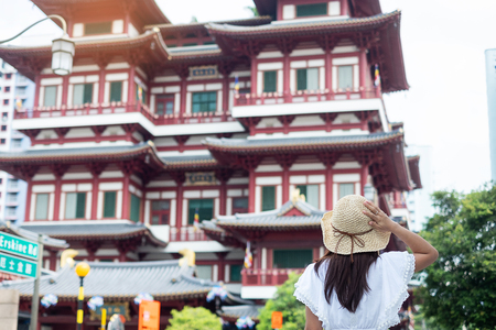 Woman traveling with white dress and hat, Asian traveler looking to Buddha Tooth Relic Temple