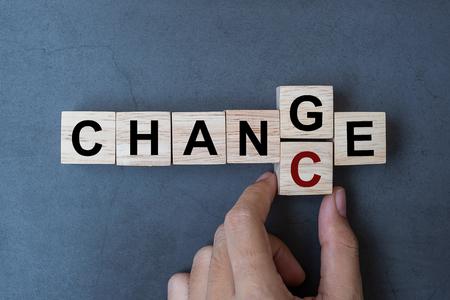 Geschäftsfrau-Hand, die hölzernen Würfel mit Flip-Block hält ÄNDERUNG zu CHANCE-Wort auf Tabellenhintergrund. Erfolgs-, Strategie-, Lösungs-, Geschäfts- und positive Denkkonzepte