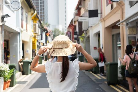 Young woman traveling with white dress and hat, happy Asian traveler walking