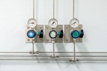 Válvulas de tuberías de nitrógeno, helio, oxígeno (aire cero) y medidor de presión de gas con regulador para controlar el proceso de producción de presión de medida en la sala del laboratorio de química