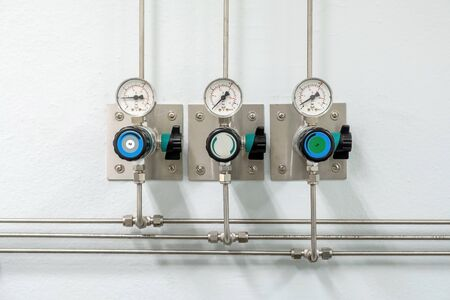 Valves of nitrogen, Helium, Oxygen ( Air Zero) pipes and Gas Pressure Meter with Regulator for monitoring measure pressure production process in Chemistry Laboratory room