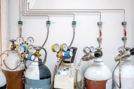 Valves of nitrogen, Helium, Oxygen ( Air Zero) tank and Gas Pressure Meter with Regulator for monitoring measure pressure production process in Chemistry Laboratory room Stock fotó