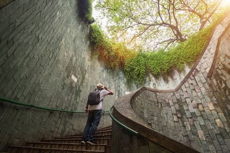 young man tourist traveling and standing on underground spiral staircase at  Park 免版税图像