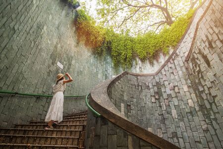 Young Woman tourist traveling and standing on underground spiral staircase at Park