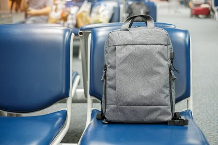 gray business backpack on seat at the interior of airport terminal. Business and Travel concept