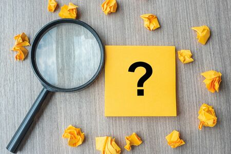 Questions Mark word on yellow note with crumbled paper and magnifying glass on table background.