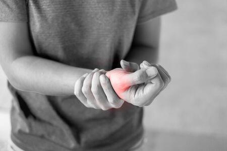Jeune femme tenant sa douleur au poignet parce qu'elle utilise un ordinateur depuis longtemps. Concept de maladie et de soins de santé Banque d'images