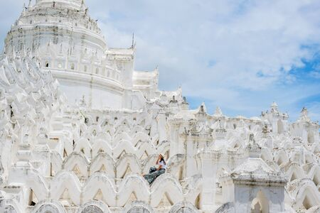young woman traveling with bag visit Hsinbyume Pagoda (Mya Thein Dan) or called white Taj Mahal of Irrawaddy river, located in Mingun, Sagaing region near Mandalay, Myanmar. landmark and popular
