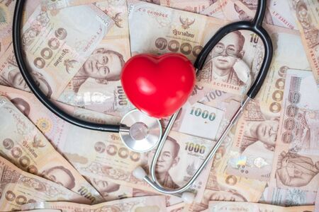 money, red heart shape and Cardiology Stethoscope on blue wood table background. business, finance, retirement and money Saving for healthcare and medical concepts