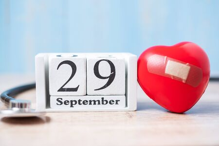 September 29 of white calendar and Stethoscope with Red heart shape on wooden background. Healthcare, life Insurance and World Heart Day concept