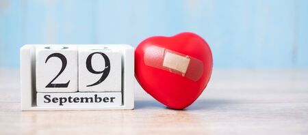 September 29 of white calendar and Red heart shape on wooden background. Healthcare, life Insurance and World Heart Day concept Stock Photo