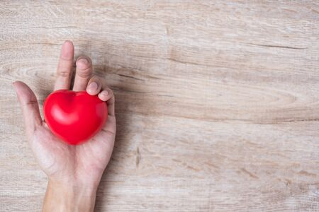 man holding Red heart shape on wooden background. Healthcare, life Insurance and World Heart Day concept