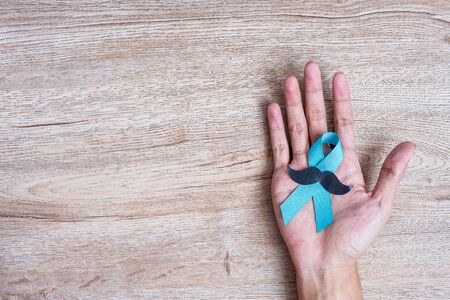 Prostate Cancer Awareness, Man holding light Blue Ribbon with moustache on wooden background for supporting people living and illness. Men Healthcare and World cancer day concept Фото со стока
