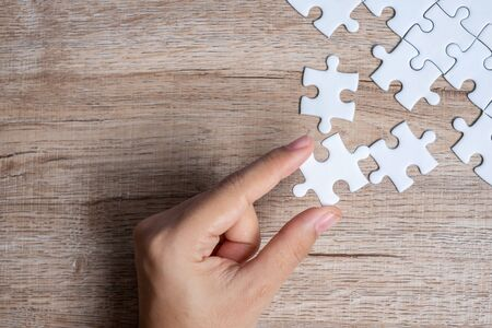 Businessman hand connecting puzzle piece. Business solutions, mission target, successful, goals, cooperation, partnership and strategy concept