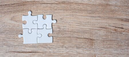puzzle pieces on wood table background. Business solutions, mission target, successful, goals, cooperation, partnership and strategy concept