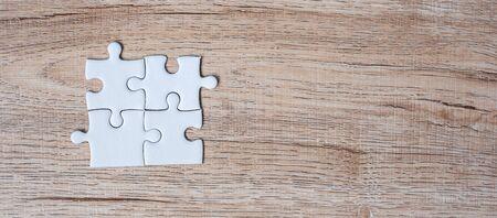 Puzzleteile auf Holztisch Hintergrund. Geschäftslösungen, Missionsziel, erfolgreich, Ziele, Kooperation, Partnerschaft und Strategiekonzept