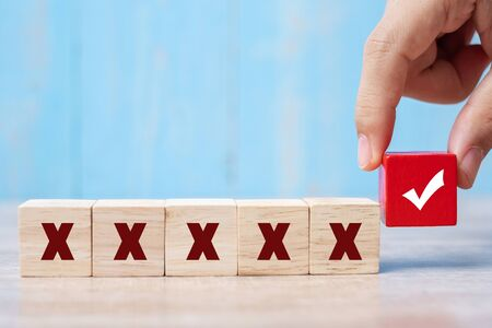 homme d'affaires tenant un bloc de cubes de bois avec un symbole correct différent du symbole incorrect sur fond de table