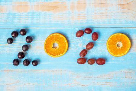 2020 Happy New Year and New You with fruits, Black grapes, Orange, Red grapes on blue wood background. Goals, Healthy, Healthcare, Resolution, Time to New Start, fitness and dieting concept. Stock Photo