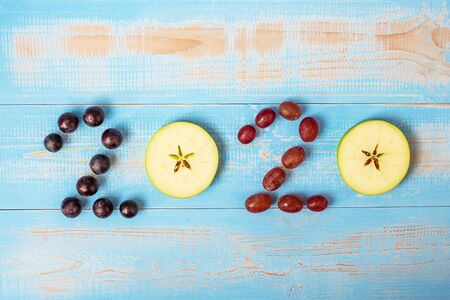 2020 Happy New Year and New You with fruits, Black grapes, Red grapes and green apples on blue wood background. Goals, Healthy, Healthcare, Resolution, Time to New Start, fitness and dieting concept.
