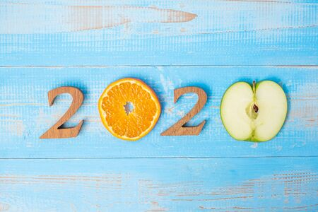 2020 Happy New Year and New You with green apple and Orange fruits on blue wood background. Goals, Healthy, Healthcare, Resolution, Time to New Start, sport, fitness and dieting concept.