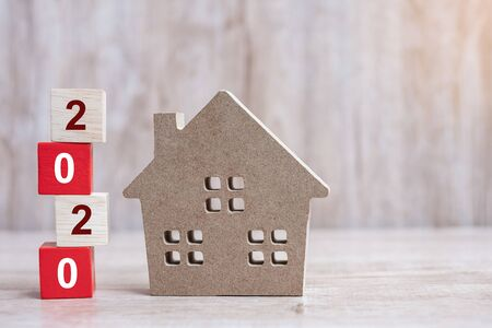 2020 Happy New Year with house model on wooden background. Banking, real estate, investment, financial, savings and New Year Resolution concepts