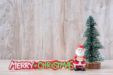 Christmas decoration, snowman, Santa claus and pine tree  on wooden table background, preparation for holiday, Happy New Year and Xmas Concept