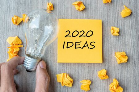 2020 Idea words on yellow note and crumbled paper with Businessman holding lightbulb on wooden table background. New Year New Start Creative, Innovation, Imagination, Resolution and Goal concept