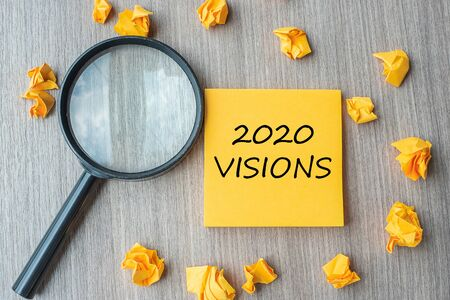2020 VISIONS words on yellow note with crumbled paper and magnifying glass on wooden table background. New Year New Start, Idea, Strategy, and Goals concept Stok Fotoğraf - 133018369