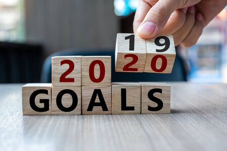 Business man hand holding wooden cube with flip over block 2019 to 2020 Goals word on table background. Resolution, strategy, solution, goal, business and New Year holiday concepts 스톡 콘텐츠