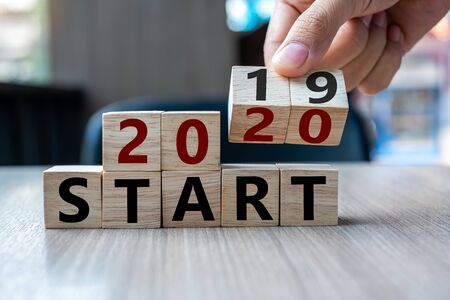 Business man hand holding wooden cube with flip over block 2019 to 2020 Start word on table background. Resolution, strategy, solution, goal, business and New Year holiday concepts