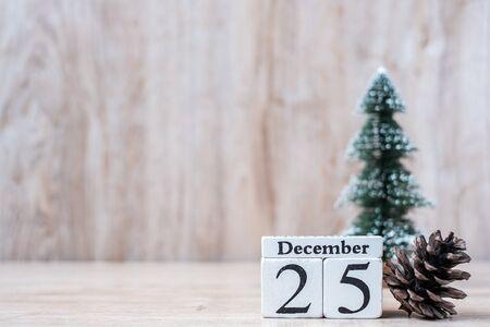 25. Dezember-Kalender mit Weihnachtsdekoration, Schneemann, Weihnachtsmann und Kiefer auf Holztischhintergrund, Vorbereitung auf Urlaub, Frohes neues Jahr und Weihnachtskonzept
