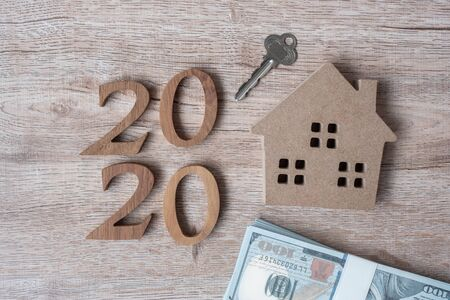 2020 Happy New Year with house model and money on wooden background. Banking, real estate, investment, financial, savings and New Year Resolution concepts Stockfoto