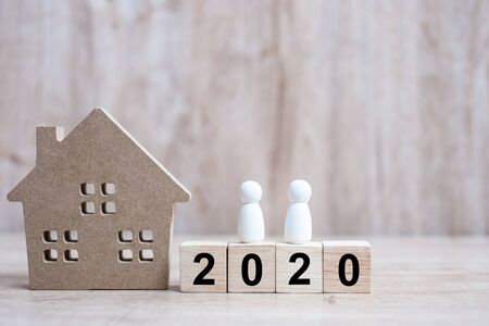 2020 Happy New Year with house model and people  on wooden background. Banking, real estate, investment, financial, savings and New Year Resolution concepts