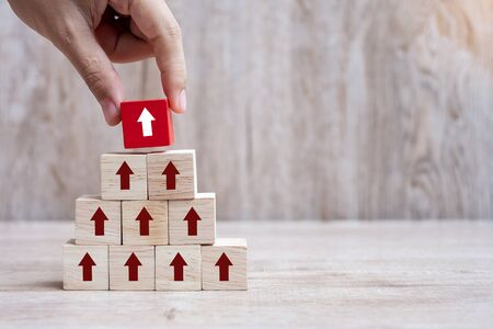 Businessman hand placing or pulling Red arrow wooden block on table background. Business Growth, Improvement, strategy and Successful Concepts